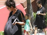 Maternity wear: Halle Berry's dress got caught in the wind, showing its maternal style, as she picked up her daughter Nahla (left) from school in Los Angeles, California on Monday