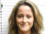 Pictured: Teen Mom 2 star Jenelle Evans smiles in her mug shot as she turns herself in to police for arrest warrant after missed cyberstalking court hearing