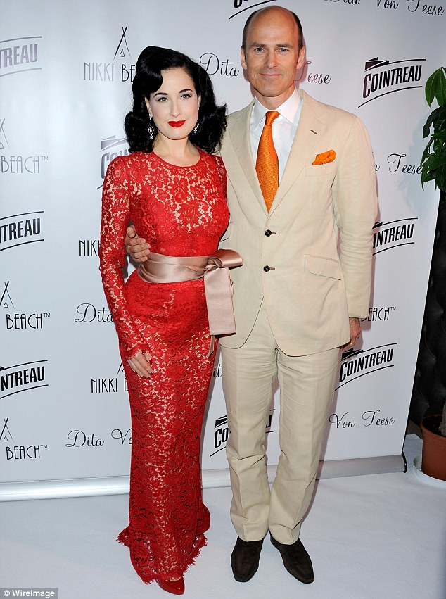 Cosy up: The burlesque dancer posed with Cointreau Managing Director Justin Weston for a photo on the carpet