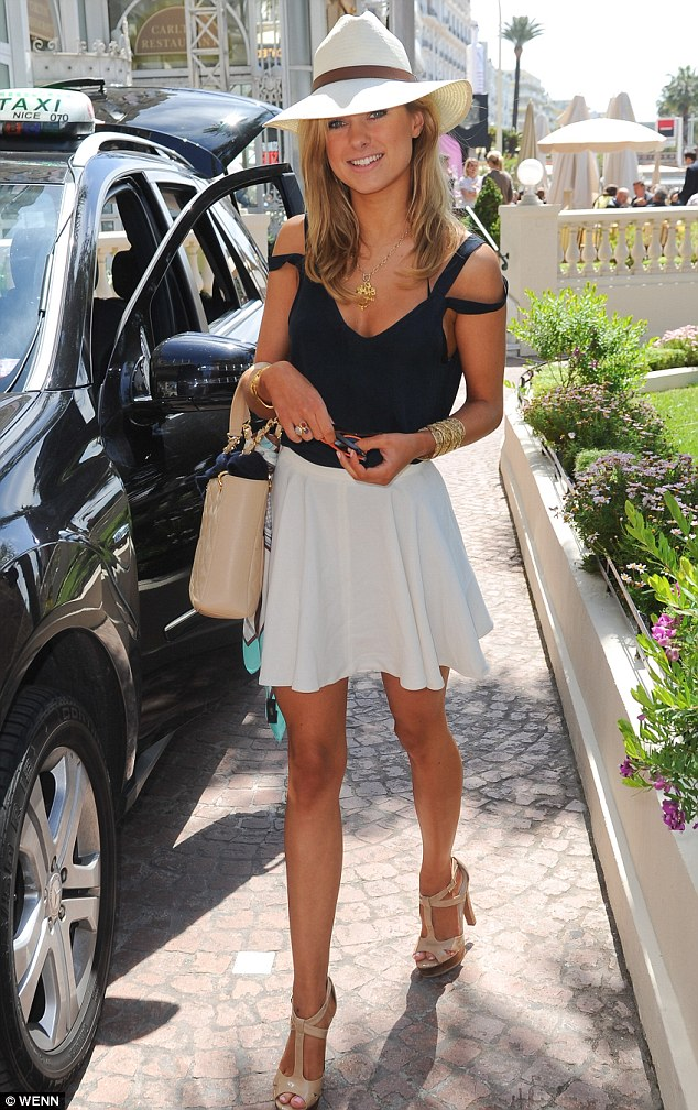 Touching down: Kimberley Garner arrived in Cannes on Tuesday wearing a flirty white miniskirt and revealing black vest top