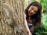 Peek-a-boo: The squirrel and the actress actually got quite close as she peered around the trunk of a tree