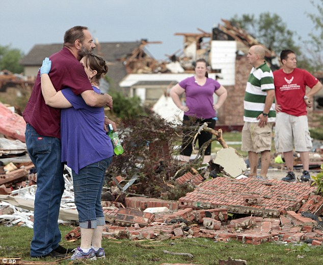 Horrific: At least 20 children have been reported dead following the devastating tornado. This man hugs his neighbor outside her home