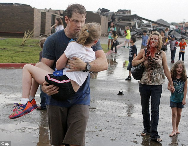 Horrific: Teachers carry children away from Briarwood Elementary school after the tornado destroyed the school.