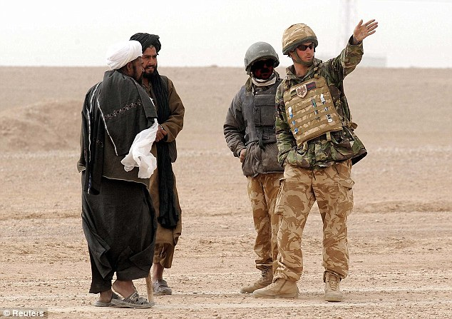 An Afghan interpreter, his face masked for security purposes, pictured with Prince Harry in 2008 . Up to 600 Afghans who have worked as interpreters are to be given the right to move to Britain