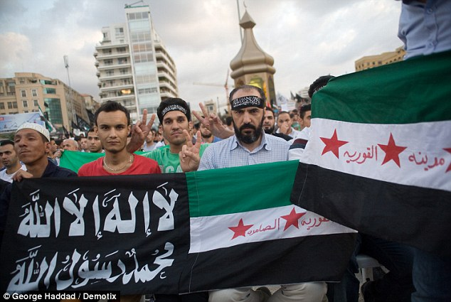The Syrian and Muslim Jihad flag is held in front of a mosque in Beirut against a cartoon mocking the Islamic prophet Mohammad in a rally held by Sheikh Ahmed al-Asirin in protest against the anti-Islam film and offensive cartoon