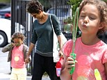 Smelling the flowers: Nahla Aubry stopped to get in touch with nature on Wednesday as mother Halle Berry dropped her off at school and later blew bubbles for doting dad Gabriel Aubry