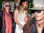 The luckiest girl in the world! Johnny Depp tenderly places a hand on Amber Heard's arm as they dine with The Rolling Stones