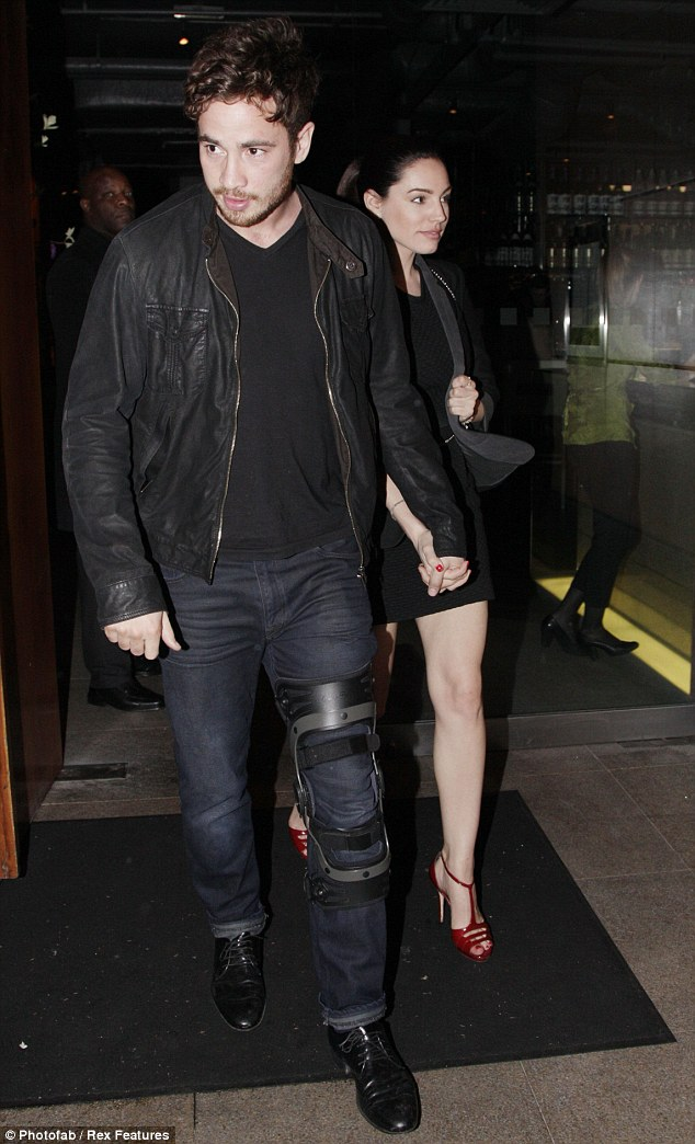 Hop along: Danny Cipriani sported a large knee brace as headed for dinner with his girlfriend Kelly