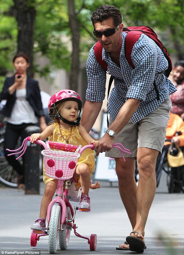 A doting father: Jason Hoppy, estranged husband of reality star Bethenny Frankel, put on a happy face on Friday to take their daughter Bryn for a spin on her adorable pink bicycle around New York