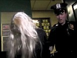 Police escort: An officer walked with the handcuffed Bynes out of the New York City police station