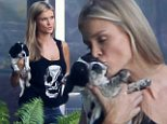 'And they called it puppy love!' Model Joanna Krupa smothers her dog with kisses as she carries her close to her heart