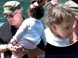 Doting dad: Robert De Niro, 70, held baby daughter Helen Grace on Thursday as his family travelled by boat in Italy