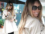 Singer in the rain! Mariah Carey dons flirty trench coat as she keeps dry under giant umbrella