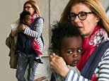 Mum on the run! Makeup-free Connie Britton carries son Yoby in sling as she dashes through airport