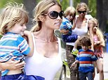 They're in good hands: Denise Richards tenderly cradles Charlie Sheen and Brooke Mueller's twins as she takes them to school