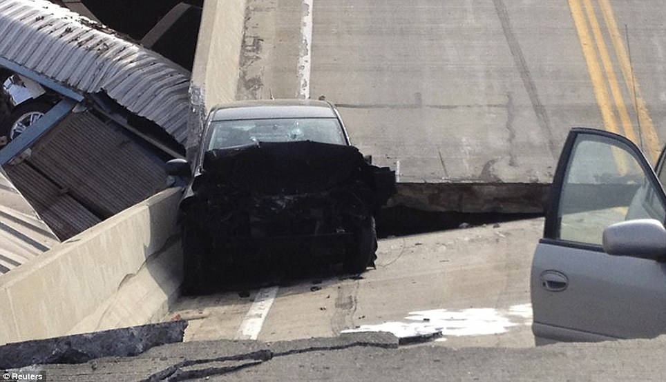 Lucky escape: Only two cars were using the overpass as it collapsed after the derailed rail cars knocked a support post