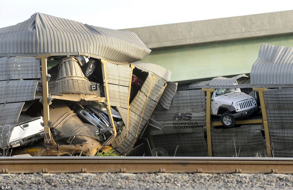 New vehicles being transported on a Burlington Northern Santa Fe train poke out of their damaged rail car after a Union Pacific train collided with it