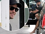Still a beach boy at heart! Liam Hemsworth wanders barefoot into a Hollywood gym... and proves he's still in good spirits with a sneaky grin