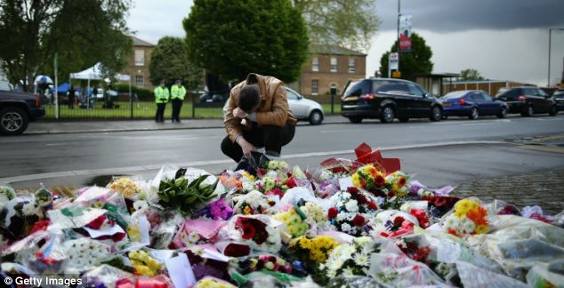 A man contemplates at a scene where flowers lay