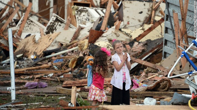 Two girls stand in rubble in Moore.