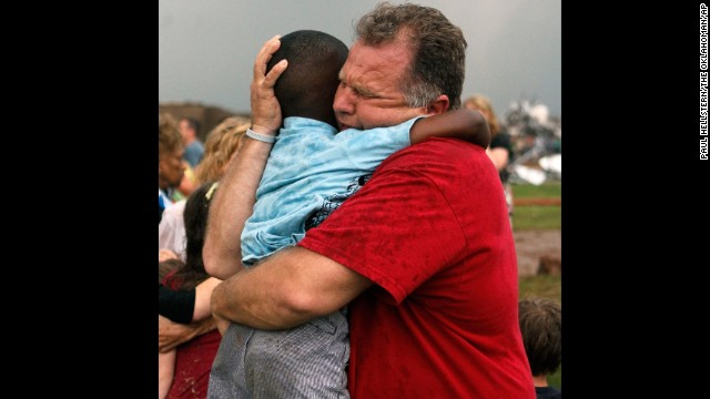 Jim Routon hugs his neighbor, 7-year-old Hezekiah, after the tornado strikes on May 20. An earlier version of this caption incorrectly stated that Routon was Hezekiah's teacher. <a href='http://outfront.blogs.cnn.com/2013/05/21/neighbors-comfort-boy-in-tornado-aftermath/'>See an interview with the pair.</a><strong> </strong>