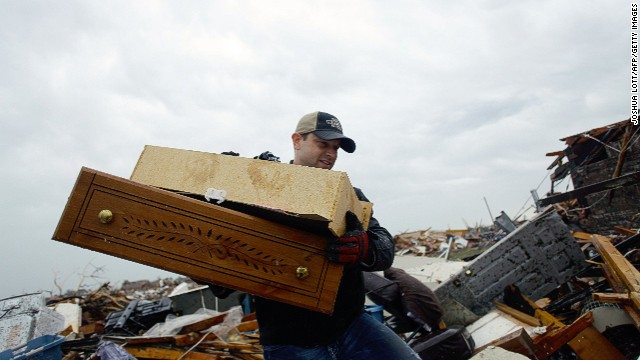 A man helps move a resident's belongings from a destroyed home on May 21 in Moore.