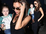 Her little doll! Victoria Beckham carries mini fashionista daughter Harper as she jets into Los Angeles with her brood