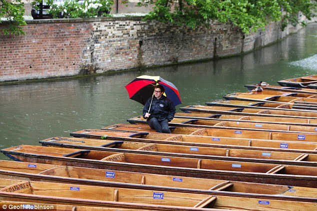 Bad for business: Punt operator Niall Folbigg had little to do today but sit and hope for the rain to clear from the River Cam in Cambridge today