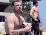Surf's up: Liev Schreiber shows off his muscular physique as he strips off his wetsuit following surf session