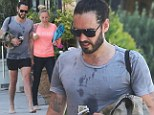Sweaty and shoeless: Russell Brand looks more hippie than Hollywood as he enjoys some yoga with a blonde