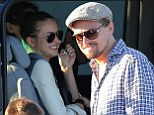Under his spell! Leonardo DiCaprio has new model 'girlfriend' Toni Garrn in fits of giggles as they head to the airport together