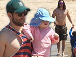 Battle of the biceps! Max Greenfield and Steve Howey flex their muscles as they hit the beach in Hawaii with their families