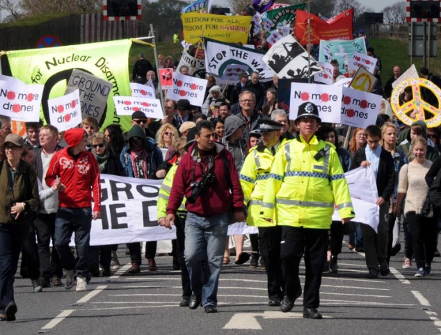 Protest: Campaigners march to RAF Waddington, Lincolnshire, which started flying armed drones over Afghanistan this week