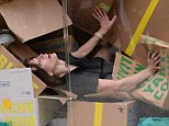 As you do: Model and actress Milla Jovovich turns herself into a living piece of artwork in Venice on Wednesday as she immerses herself in numerous cardboard boxes