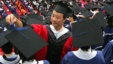 A man adjusts a student's mortar board during the graduation ceremony at Fudan University in Shanghai, June 28, 2006. (File)