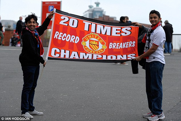 Never in doubt: United fans hold up flags and scarves before the match against Aston Villa