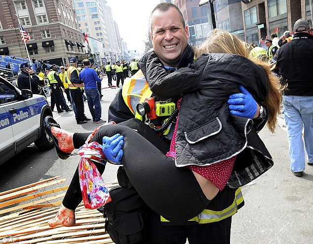 Getting treatment: Boston firefighter James Plourde carried one of the more than 180 injured away from the scene