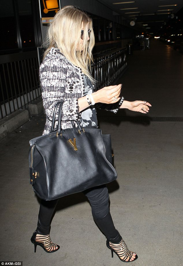 No slowing down: The singer, who is set to welcome her first child this summer, carried a large YSL handbag on the flight