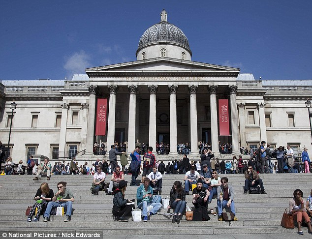 Warm: Revellers sit on the steps outside the National Gallery in Trafalgar Square, central London today