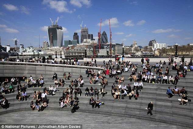 Soaking up the sun: City workers enjoy the sunshine in London today against the city backdrop as temperatures hit 20C
