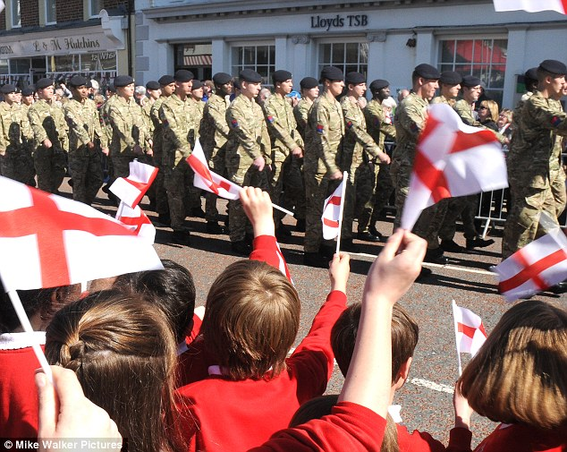 Patriotism: Schoolchildren from Thornley Island Junior School in Emsworth, West Sussex, wave English flags as soldiers from the 47 Regiment Royal Artillery march today