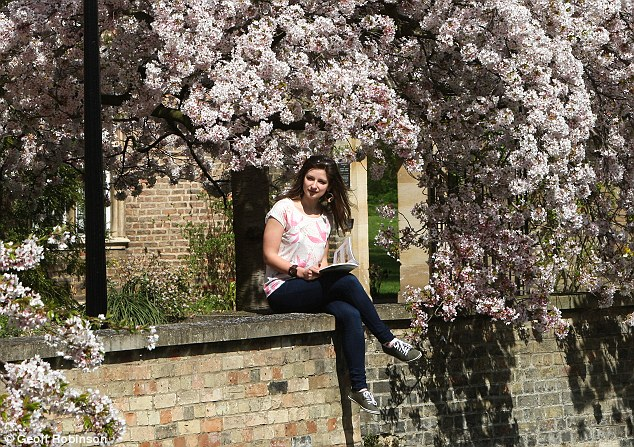 Hot day: Student Viktoria Ruskyte sits among the cherry blossom enjoying the warm weather by the River Cam in Cambridge today