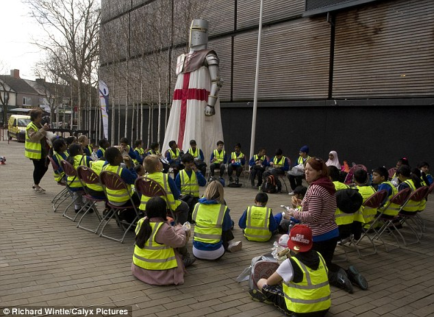 Eating outside: Children enjoy their lunch under the watchful eye of St. George in Swindon's Wharf Green