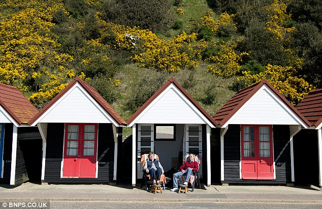 Warm weather at last: A couple soak up the sun outside their beach hut at Bournemouth today