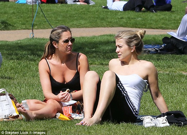 Warm weather: Two women enjoy the sunshine in Green Park, London, today as temperatures were set to hit 20C