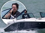 'Thinking about taking the summer off line': Rosie O'Donnell applies sunscreen while on a solo boat outing in Miami