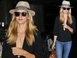 Flying high and low: Rosie Huntington-Whiteley takes the plunge in flirty black top for her 11-hour flight