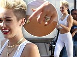 She's not giving up that ring! Miley Cyrus defiantly flashes her engagement sparkler as she slips into tight white lycra