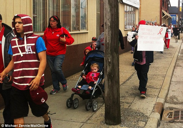 People walk during a rally for Michelle Knight on Saturday in Cleveland, the sign reads 'Get well Michelle! stay strong! We support you!'