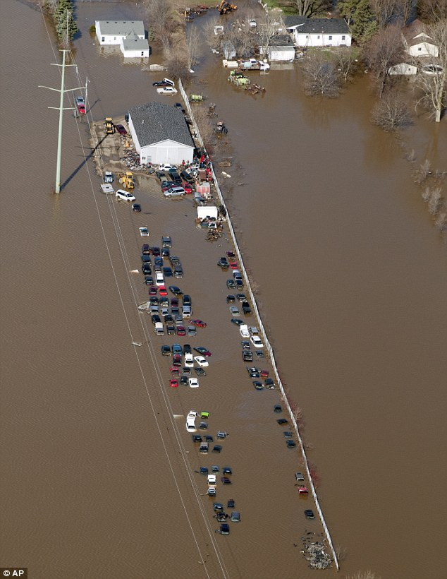 An automobile scrapyard in James Township, Michigan near the Tittabawassee River is flooded